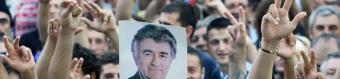 Los manifestantes muestran un retrato de Karadzic y realizan un saludo serbio. (Foto: AP) MÁS FOTOS