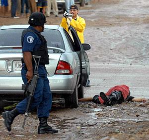 Un policía patrulla junto al cadáver de un hombre asesinado. (Foto: EFE)