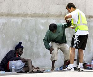 Un miembro de los servicios sanitarios junto a dos de los inmigrantes. (Foto: EFE)