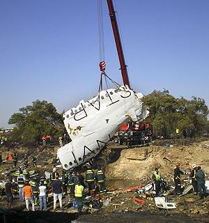 Miembros de los equipos de rescate observan cómo una grúa levanta lo que queda del fuselaje destrozado del Spanair JK 5022. (Foto: EFE)