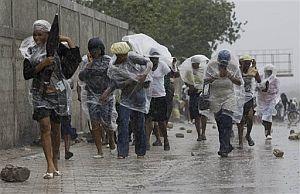 Algunas personas tratan de protegerse de las lluvias en Puerto Príncipe. (Foto: AP)
