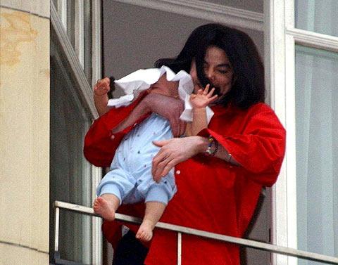 El cantante, sosteniendo a su hijo en el balcón del Aldon de Berlín. (Foto: EFE)