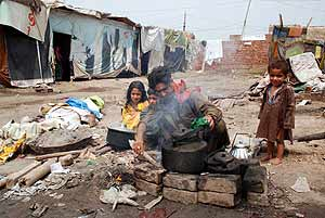 Un grupo de refugiados afganos cocinan en Pakistán (Foto:ELMUNDO).