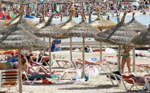 Fotografía de archivo de una playa balear llena de hamacas y sombrillas de pago.