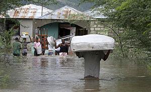 Unos haitianos transportan sus enseres en Artibonite. (Foto: AP)