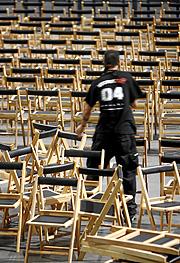 Un operario coloca en perfecto orden las sillas.