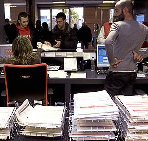 Dos jóvenes solicitan la ayuda en la Oficina de Avda. de Asturias en Madrid. (Foto: C. Alba)