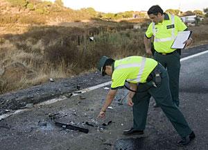 Dos agentes de la Guardia Civil de Tráfico realizan el atestado del accidente de Huelva. (Foto: EFE | Julián Pérez)