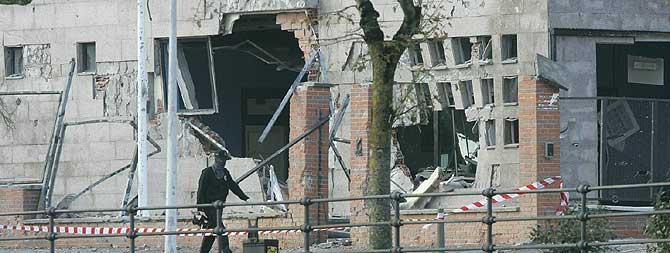 Un agente busca evidencias frente a los boquetes causados por el atentado. (Foto: Carlos García)