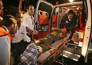 Miembros de los equipos de emergencias suben a uno de los soldados heridos a la ambulancia. (Foto: AP)