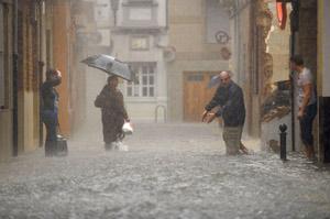 Varios vecinos asisten a la corriente de agua que pasa ante sus casas en Sueca (Valencia). (Foto: Kai Försterling).
