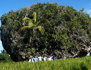 Varias personas posan junto a uno de los bloques de coral arrastrados hasta el centro de la isla de Tongatapu por el tsunami y cubierto de vegetación por el paso del tiempo. (Foto: GSA)