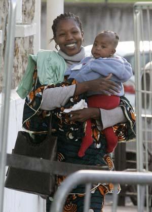 Madre inmigrante con su hijo en brazos sonríe en una localidad cercana a París. (Foto: Reuters)