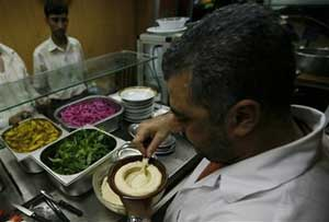 Un cocinero libanés prepara un plato de 'hummus' en un restaurante de Beirut. (Foto: AP)