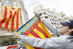Un joven con la senyera valenciana increpa a los miembros de Esquerra que han desplegado una enorme bandera independentista. (Foto: Vicent Bosch)  [Vea más fotos]