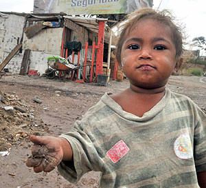 Un niño juega con lodo en Tegucigalpa, Honduras. (Foto: Gustavo Amador)