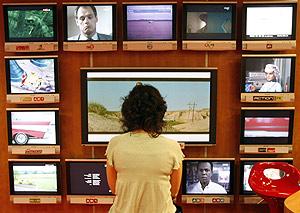 Una visitante al Mipcom observa varias pantallas de televisión. (Foto: Reuters)