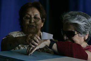 Dos mujeres votan en el Estadio Nacional de Santiago. (Foto: EFE)