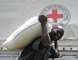 Un hombre acarrea ayuda d cruz Roja en Kibati. (Foto: AFP)