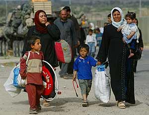Refugiados iraquíes caminan después de pasar un puesto de control. (Foto: Kevin Frayer)