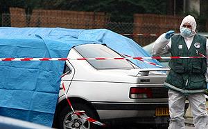 Un policía forense examina el vehículo donde fueron tiroteados los agentes. (Foto: AP)