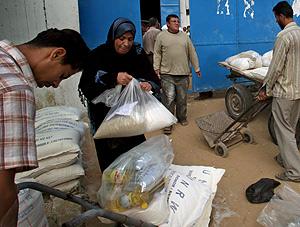 Varios palestinos recogen alimentos en un centro de ayuda de la ONU. (Foto: EFE)