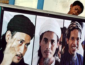 Un niño mira las fotos de tres condenados a muerte en Bali. (Foto: EFE)