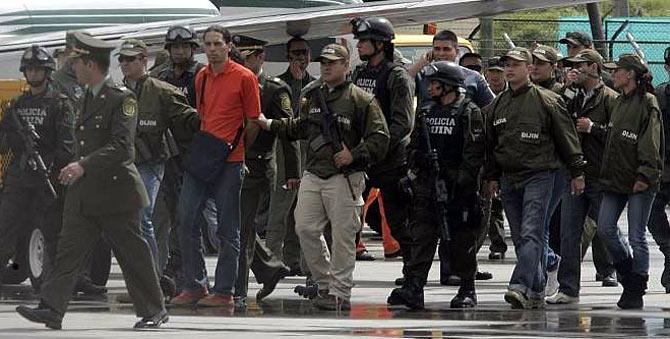 David Murcia, durante su extradición a Colombia, rodeado de varias decenas de policías. (Foto: EFE)