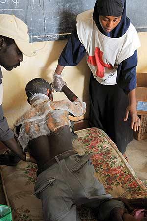 Personal de Cruz Roja asiste a una víctima de los disturbios en Jos. (Foto: AFP)