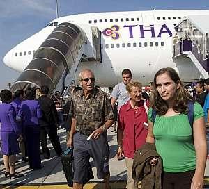 Los pasajeros del primer avión que aterriza en el aeropuerto de Suvarnabhumi descienden de la nave. (Foto: EFE)