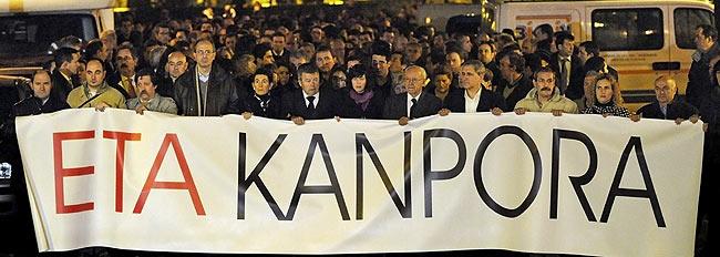Dos hermanos del fallecido, Imanol y José María, y una de sus hijas, Jaione, entre otras personas, portan la pancarta de la manifestación posterior al funeral donde se lee 'ETA fuera'. (Foto: AFP)