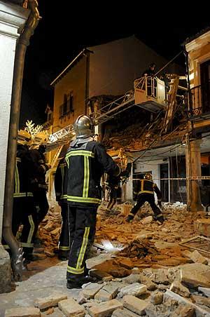 Los bomberos, durante el rescate en la vivienda que explotó. (Foto: EFE)