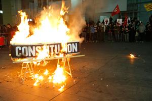 Un encapuchado ha quemado un ataúd en el que se podía leer la palabra 'Constitución'. (Foto: Santi Cogolludo)