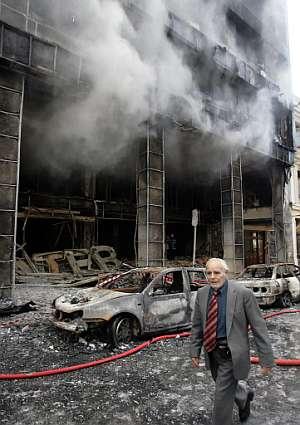 Un hombre pasa delante de una tienda calcinada por el fuego en Atenas. (Foto: AFP)