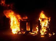 Un coche incendiado en una calle. (EPA)
