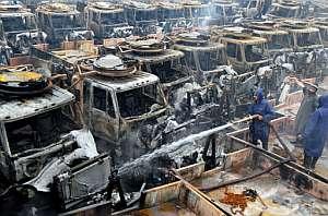 Bomberos paquistaníes enfrían con agua los restos humeantes de los vehículos. (Foto: AP)