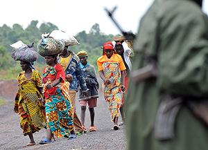 Congoleños huyen de Kibati observados por un combatiente. (Foto: AFP)