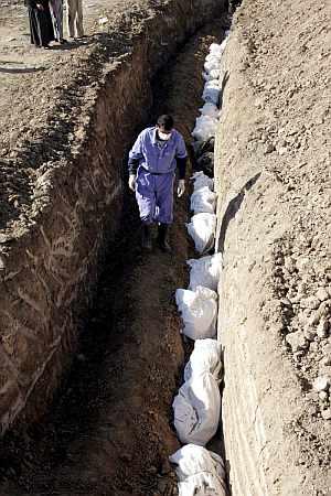 Unos trabajadores entierran en Irak. en una fosa común los restos mortales de unas 110 personas no identificadas. (Foto: EFE)