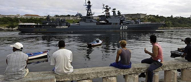 Varios cubanos observan con expectación la presencia de un imponente navío ruso. (Foto: AFP)