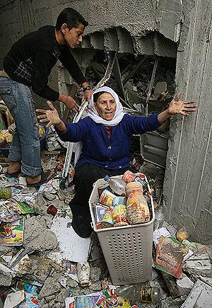 Una mujer con su hijo tratan de recuperar sus pertenencias de su casa atacada. (Foto: AFP)