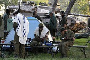 Soldados israelíes hacen un rito religioso junto a los tanques. (Foto: AFP)