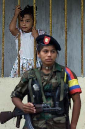 Una niña mira a una adolescente que hace guardia con un rifle. (Foto: AP)