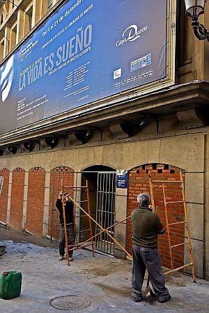 Dos operarios retiran los andamios tras terminar de tapiar con ladrillos las puertas de acceso al teatro. (Foto: EFE)