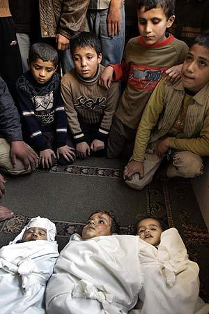 Varios niños palestinos miran los cadáveres de otros tres fallecidos por los ataques israelíes. (Foto: AP)