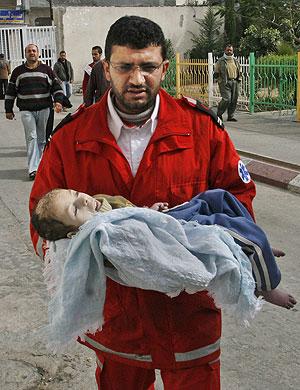 Un miembro de la Cruz Roja palestina lleva a un niños herido en Beit Lahia. (Foto: AP)
