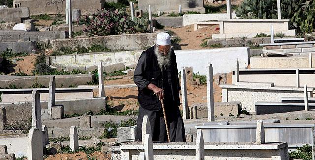Un palestino en el cementerio de Sheik Radwan, dañado en los ataques israelíes sobre la ciudad de Gaza. (Foto: EFE)
