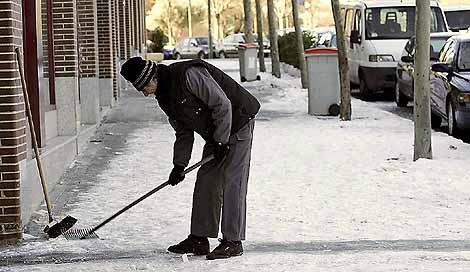 Un hombre golpea al hielo en la acera (Foto: Bernabé Cordón)