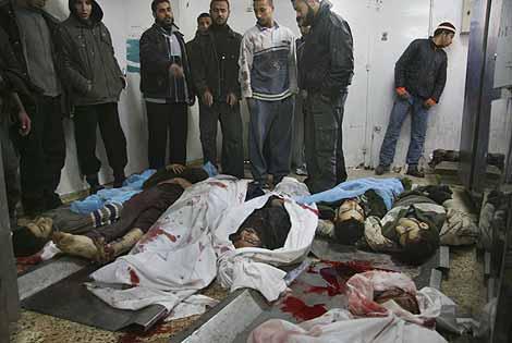 Varias personas observan unos cadáveres en la morgue del Hospita Shifa de Gaza. (Foto: AP)