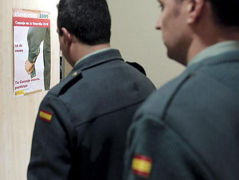 Dos guardias civiles frente a un cartel electoral. (Foto: EFE)