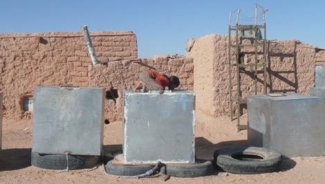 Una niña bebe agua de uno de los bidones que abastacen a los saharauis | A. Lozano)